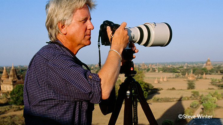 Steve Winter peering through a camera with a telephoto lens.