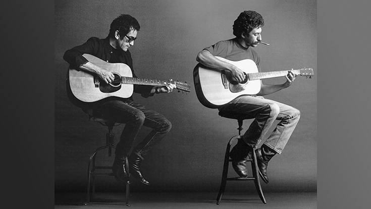 Two men play guitar while seated on stools.