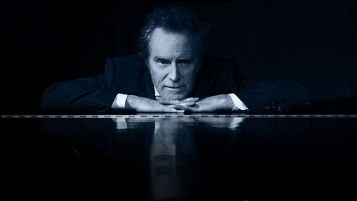 Headshot of JD Souther at the piano under a blue glow.