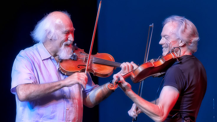 Michael Doucet and Tom Rigney playing fiddles side-by-side.