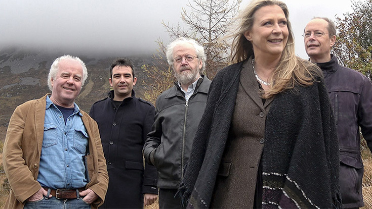 Members of Altan posing in front of a foggy landscape.