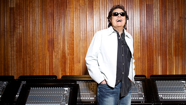 Ronnie Milsap in white jacket and sunglasses in front of a bank of soundboards.
